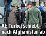 Flüchtlinge besteigen neben türkischen Sicherheitsbeamten einen Bus