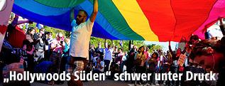 Menschen unter einer Regenbogenfahne