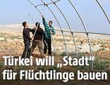 Syrische Flüchtlinge bauen Zeltstangen zusammen