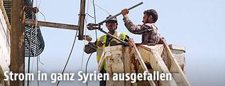 Syrische Elektriker auf einer Hebebühne arbeiten an einem Strommasten