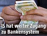 Eine Person hält syrische Banknoten