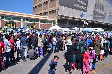 Flüchtlinge stehen vor einer Essensausgabe im Hafen von Piräus Schlange
