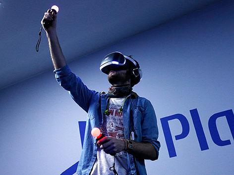 Mann mit PlayStation VR Headset und Move-Controllern