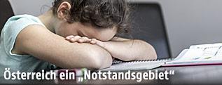 Mädchen senkt Kopf auf Arme am Schreibtisch