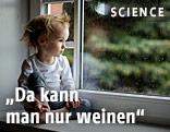 Kleines Kind sitzt am Fenster und schaut hinaus