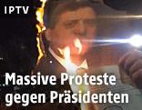 Demonstranten zünden ein Foto des Präsidenten an