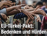 Flüchtlinge halten Hände über Zaun