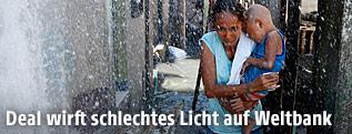 Frau in Manila geht im Wasserregen einer defekten Wasserleitung