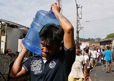 Philippinischer Mann in Manila trägt einen Wasserkanister