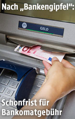 Frau behebt Geld an einem Bankomat