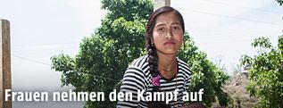 Nepalesisches Mädchen sitzt auf einer Mauer