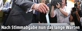 Politiker wirft seinen Stimmzettel in eine Urne
