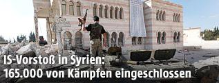 Kämpfer steht auf einem Panzer vor einer zerstörten Moschee in Asas