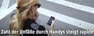 Frau überquert einen Zebrastreifen während sie eine SMS in ihr Handy tippt