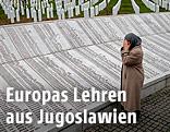 Frau an einer Gedenkstätte der Jugoslawienkriege