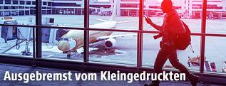 Passagier am Weg zum Gate, im Hintergrund ein Flugzeug