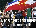 Ein Mann trägt eine Jugoslawien-Fahne
