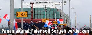Feiernde Menschen vor dem Kontainerschiff Cosco Shipping Panama