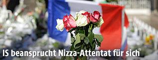 Blumen vor einer französischen Fahne