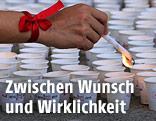 """PErson mit einem """"Red Ribbon"""" am Handgelenk zündet Kerzen in Bechern an"""