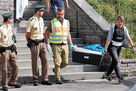 Polizisten tragen Beweisstücke
