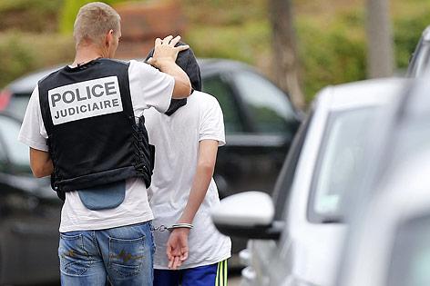 Ein französischer Polizist führt einen Mann mit Kapuze und Handschellen ab
