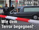 Polizisten und ein Leichenwagen am Tatort in Ansbach