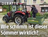 Person auf dem Heckcontainer eines Traktors, der auf einer überschwemmten Straße fährt