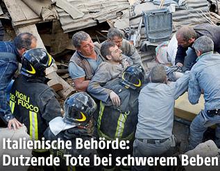 Feuerwehrleute retten einen Überlebenden aus den Trümmern