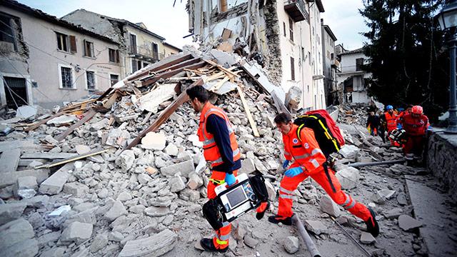 Helfer auf den Trümmern eines zerstörten Haus