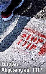"""Fuß und ein """"Stop TTIP"""" auf dem Gehsteig"""