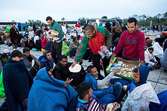 Helfer verteilen an wartende Flüchtlinge in Nickelsdorf Essen