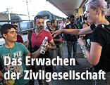 Frau reicht einem Kind am Winer Westbahnhof eine Wasserflasche