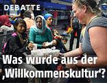 Frau reicht syrischen Flüchtlingen etwas zu trinken