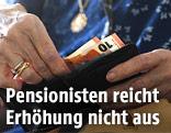 Pensionistin hält Geld in der Hand