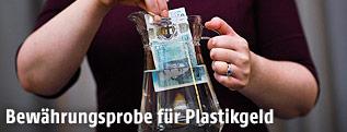 Eine neue Fünf-Pfund-Banknote aus Plastik wird in einen Krug mit Wasser getaucht