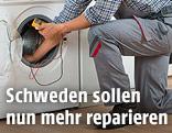 Handwerker hantiert an Waschmaschine