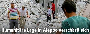 Einwohner zweischen zerstörten Häusern in Aleppo