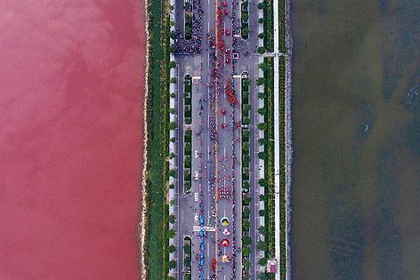 Straße über einen Salzsee in Yuncheng (China), der auf Grund von Algen auf einer Seite rot gefärbt ist