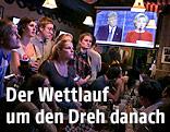 Studenten in einer Bar verfolgen das TV-Duell