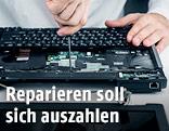 Mann repariert einen Laptop