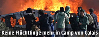 Flüchtlinge stehen vor Feuer in Calais