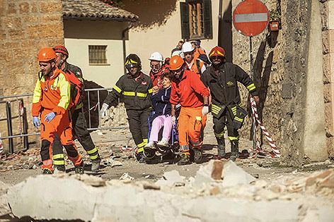 Helfer mir bergen eine Frau aus den Trümmern
