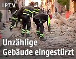 Feuerwehrmänner vor einem eingestürztem Haus