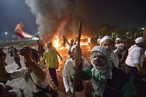 Demonstranten vor einem brennenden Auto in Jakarta