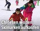 Chinesisches Mädchen lernt Ski zu fahren