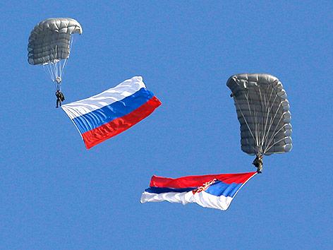 Paragleiter mit einer russischen und einer serbischen Flagge