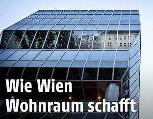 Gebäude spiegeln sich in der Fassade des Franz-Josefs-Bahnhofs