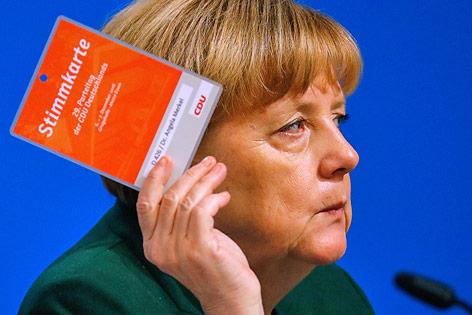 Die deutsche Bundeskanzlerin Angela Merkel mit Stimmkarte