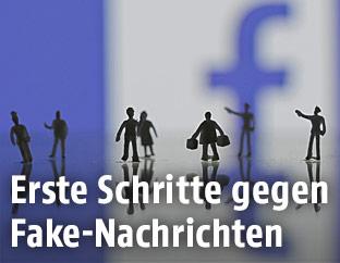 Figuren vor einem Facebook-Logo